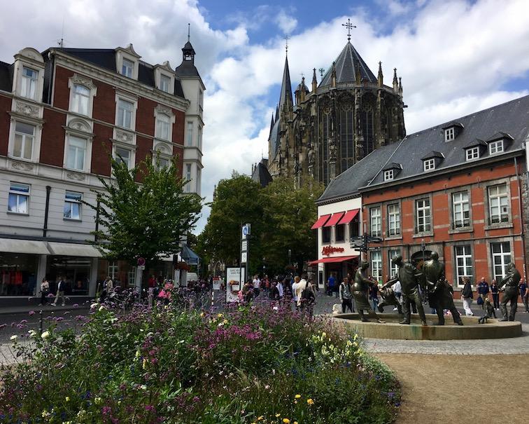 """Aachen UNESCO-Weltkulturerbe Aachener Dom Kaiserdom Aachener-Altstadt vor dem Aachener Dom und dem Brunnen """"Kreislauf des Geldes"""""""